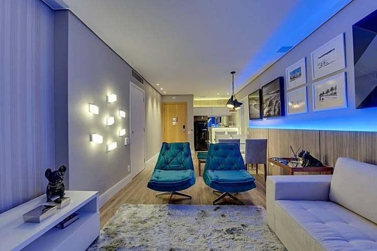 Iluminação destaca projeto moderno de flat na capital paulista: Salas de estar modernas por Guido Iluminação e Design