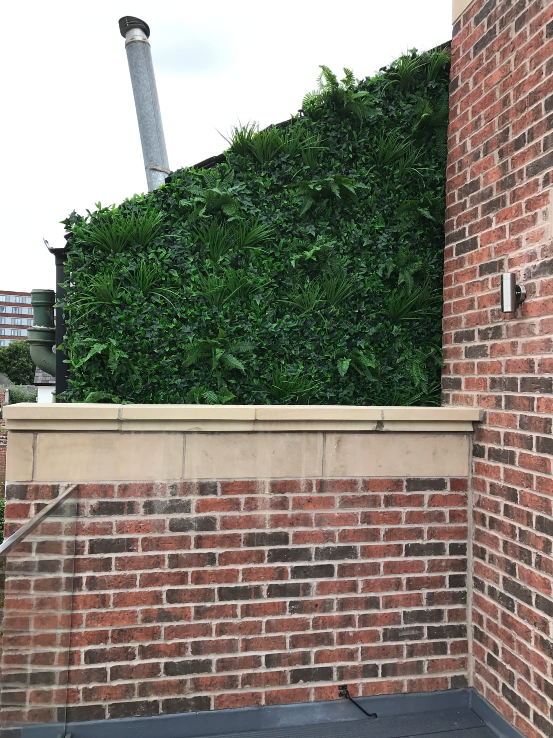 covering an ugly wall with artificial hedge for an instant vertical green wall look by hedged in