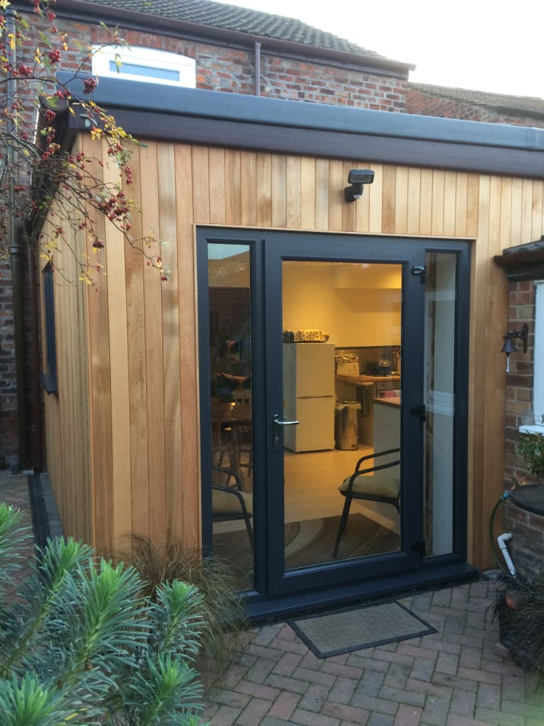 Modern Cedar Clad Timber Frame Extension On Traditional