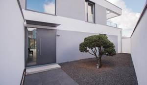 Vorgarten: minimalistische Häuser von BPLUSARCHITEKTUR