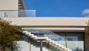 Escada de acesso ao Fitness: estrutura em metal, pisos de travertino, guarda-corpo de cristal temperado.: Casas modernas por Lanza Arquitetos