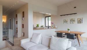 Zona living in stile minimalista con divano bianco: Soggiorno in stile  di Soffici e Galgani Architetti