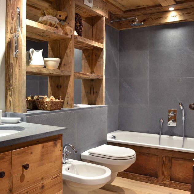 Banheiros rústicos por Andrea Rossini Architetto