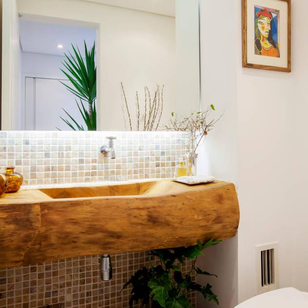 Lavabo com cuba esculpida em tora de madeira.: Banheiros rústicos por Helô Marques Associados