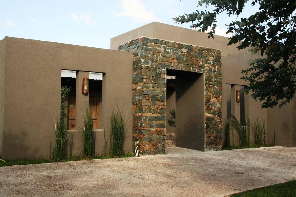 Esta casa de campo en pilar tiene todo lo que buscabas for Casas modernas revestidas en piedra