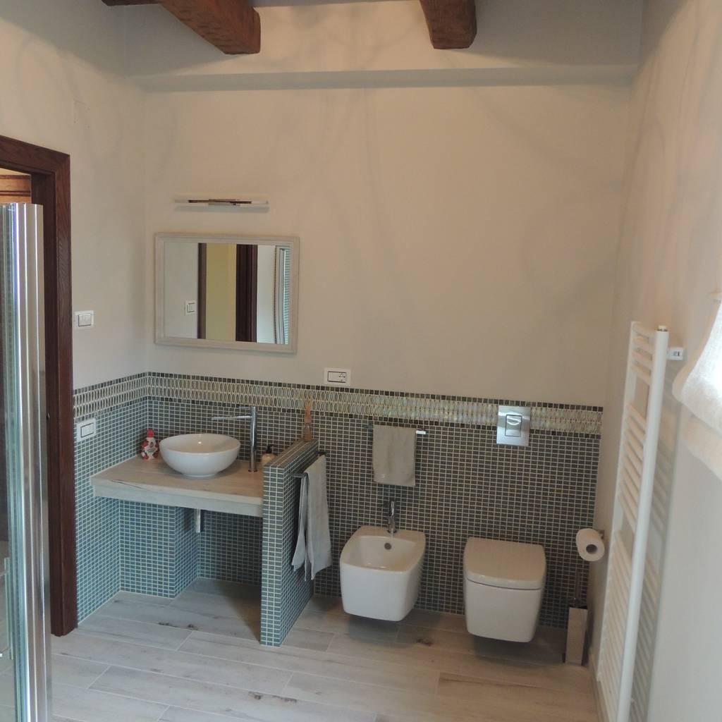 Bagno piano terra con pavimento in ceramica effetto legno - Bagno con greca ...